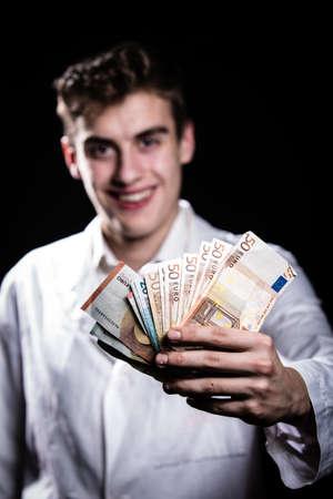 salud publica: varón medicina doctor alegre celebración en manos de euros de salario banknotes.Medic, el prestigio y el alto puesto de trabajo remunerado, la educación, el negocio de la salud pública, concept.Bribe seguro médico y el concepto de la corrupción