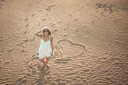 Woman on the beach making heart on the sand.Young woman walking on the sand in a white dress.Relaxed woman breathing fresh air.Travel and vacation.Freedom,inspiration,love.Birds eye view.Valentines