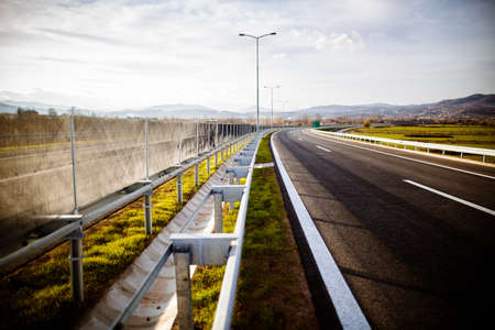 Freeway on a sunny day trough scenic green meadows.Motorway traveling long distance.Asphalt highways road in rural scene use land transport and traveling concept.Vehicular traffic. Standard-Bild