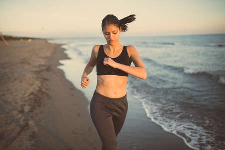 Runner woman jogging on beach in sports bra top.Beautiful fit female fitness woman training and working out outside in summer as part of healthy lifestyle.Fitness woman running at sunset on beach Stock Photo