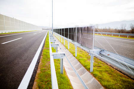 Freeway on a sunny day trough scenic green meadows.Motorway traveling long distance.Asphalt highways road in rural scene use land transport and traveling concept.Vehicular traffic.Fence.Highway bumper Standard-Bild