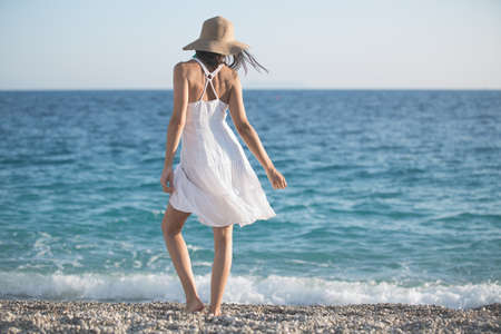 Beautiful woman in a white dress walking on the beach.Relaxed woman breathing fresh air,emotional sensual woman near the sea, enjoying summer.Travel and vacation. Freedom and inspiration concept Standard-Bild
