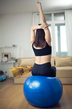 Carefree calm woman meditating.Healthy living.Enjoying peace and serenity.Beautiful fit female fitness woman practicing pilates in home.Living room for after work relaxation and exercise