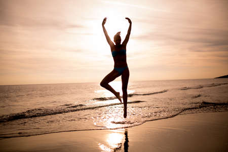 Carefree woman dancing in the sunset on the beach.Vacation vitality healthy living concept.Woman practicing yoga and meditating.Serene woman in pure happiness and enjoyment Stock Photo