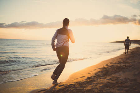 Runner woman jogging on beach in sportswear.Active fit female fitness woman training and working out outside in summer as part of healthy living lifestyle.Fitness woman running at sunset on beach