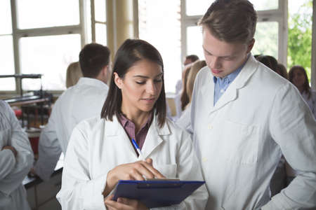 Scientific researcher holding a folder of chemical experiment research. University coworkers,Pharmacy,Medicine.Working in teams for a better result.Science project team work. Stock Photo - 52489876