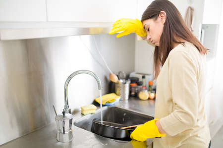casalinga: Mano cleaning.Young casalinga donna lavare i piatti in kitchen.Young donna bruna lavare i piatti a mano, a mano, indossando di gomma giallo pulizia gloves.Tired di pulizia
