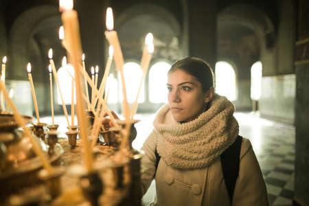 Junge weibliche Anzünden von Kerzen in einer Kirche während praying.Yellow Votivkerzen burning.Woman in St. Alexander-Newski-Cathedral.Christianity.Strong zu Gott zu beten christliche Religion und Glauben Standard-Bild - 52489882