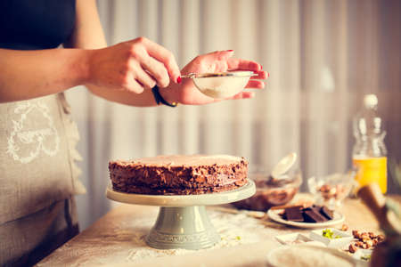 recipe background: House wife wearing apron making finishing touches on birthday dessert chocolate cake.Woman making homemade cake with easy recipe,sprinkling powdered sugar on top.Icing sugar sprinkled with colander