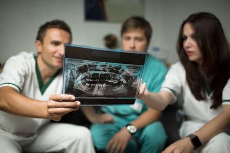 comunicacion oral: los dientes del dentista mirando sobre el cuidado X-Ray.Health digital, concepto-grupo médico y radiología de los médicos en busca de rayos x, consultar con el equipo sobre treatment.Focus en la radiografía