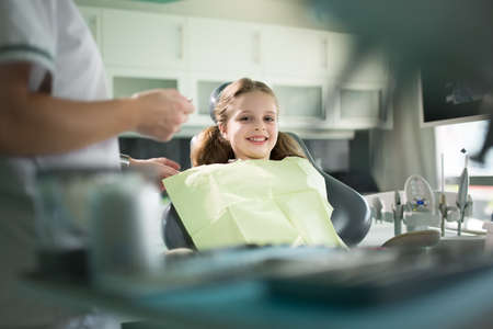 Little girl is having her teeth examined by dentist.Little girl sitting and smiling in the dentists office.Child not afraid of dentist.Dentist gives the child patient advice on dental care and hygiene 스톡 콘텐츠