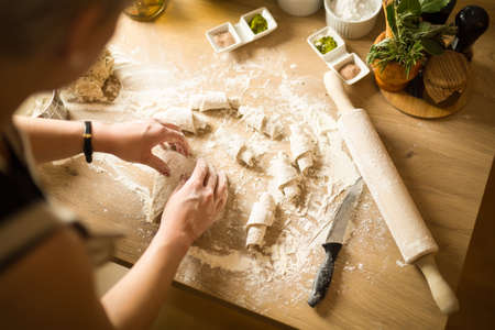 Woman cooking healthy balanced food.Carbohydrates.Whole grains.Dieting Concept.Healthy Lifestyle.Cooking food at home.Woman preparing dough for homemade puffed pastry on wooden table in the kitchen