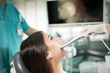 Herramientas de oficina son especialistas dentales, cámara dental oral de introducción con imagen en vivo de los dientes en el cuidado monitor.Dental, higiene dental, marque up.Dentist examina los dientes de la prevención de caries y patient.Plaque Foto de archivo - 52657379