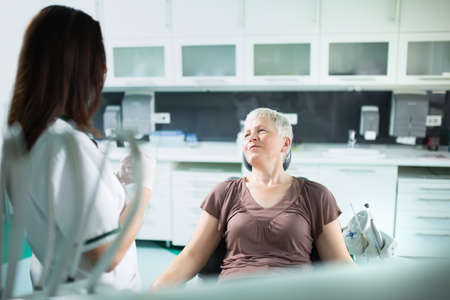 Old woman visiting the dentist taking care of her teeth.Dentist doctor talking to a senior woman patient.Dental care for elder.Prosthodontics and oral protesis