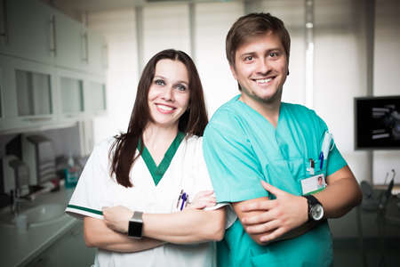 Young experienced doctor dentist standing along with his nurse assistant.Team of doctor and nurse,good teamwork and positive work team spirit concept.Doctor and dentist in dental clinic.Dental center