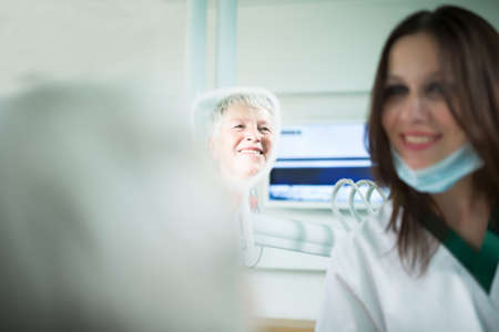 Old woman visiting the dentist taking care of her teeth.Young female dentist showing a granny her teeth,reflection in the mirror.Dentist doctor talking to a senior woman patient.Dental care for elder Stock Photo