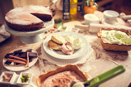 A lot of desserts on the kitchen table.Celebration,holiday sweet food.Birthday feast.Catering food,service.Cafeteria,restaurant kitchen.Homemade desserts,ice cream,chocolate cake and cookies.Recipes