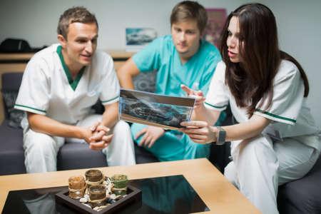 comunicacion oral: los dientes del dentista mirando sobre el cuidado X-Ray.Health digital, concepto-grupo m�dico y radiolog�a de los m�dicos en busca de rayos x, consultar con el equipo sobre el tratamiento