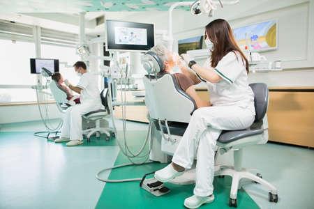 Moderne Zahnklinik mit zwei Zahnarztstühle, Zahnarzt Ärzte mit Geduld arbeiten, arbeiten in Stomatologieklinik mit zahnmedizinischen equipment.Experienced junges Team Zahn Ärzte arbeiten Standard-Bild - 52657393