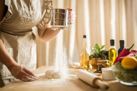 Woman preparing dough basis.Ingredients for baking.Female hands spilling powder on dough.Making dough by female hands.Cooking and baking concept
