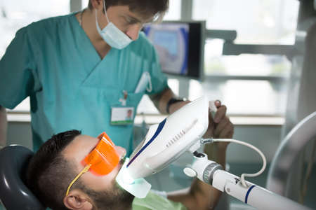 Man having teeth whitening by dental UV whitening device,dental assistant taking care of patient,eyes protected with glasses.Whitening treatment with light,laser,fluoride.Artificial teeth whitening