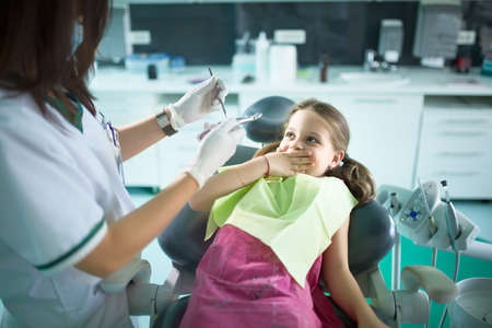 Little girl is having her teeth examined by dentist.Little girl sitting and smiling in the dentists office.Child  afraid of dentist Standard-Bild