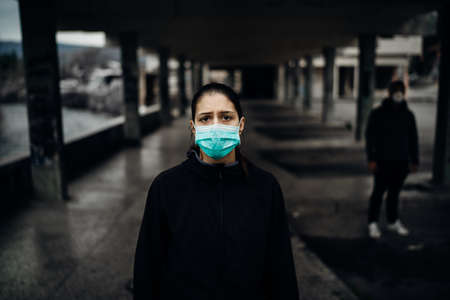 Person wearing a protective mask to prevent contagious disease spread.Life during epidemic/pandemic.Two people in abandoned place standing with distance.Sad woman affected by the infection. Stock Photo