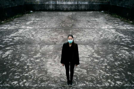 Patient suffering from infectious disease,sick person in mask.Scared woman suffering from symptoms of illness.Patient in isolation,alone in deserted unpopulated place.Incurable infectious disease
