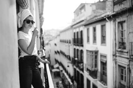 Young european woman spending free time home.Self care,staying home.Enjoying view on the balcony.Relaxing at home.Self isolation.Vacation in Europe.Narrow street in Granada,Andalucia,Spain.