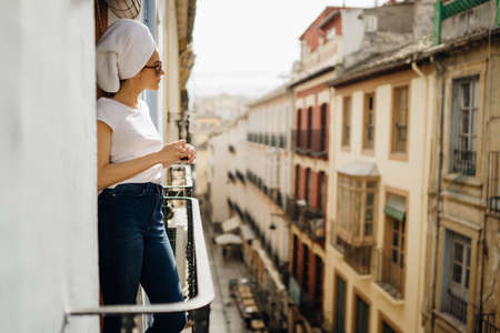 Young european woman spending spa free time home.Self care,staying home.Enjoying view on the balcony.Relaxing at home.Hotel room balcony view,luxury vacation in Europe.Morning ritual.
