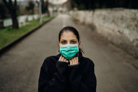 Scared sick woman wearing protective mask.Suffering from infectious disease.Infected patient suffering from symptoms of illness.Panic and fear of infection.Life in contaminated area.Nosophobia Stock Photo