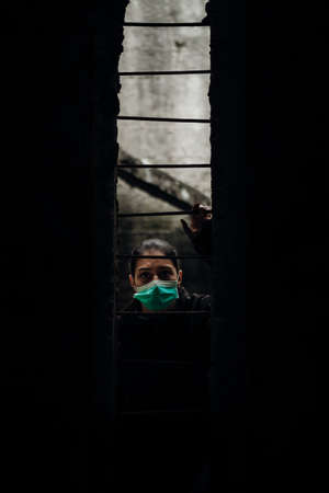 Patient quarantined for contagious lethal disease.Isolation.Prison during epidemic.Person wearing surgical protective mask in quarantine.