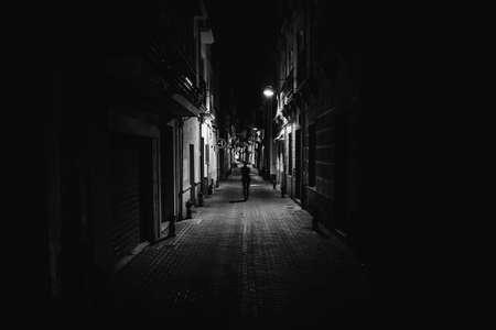 Femme marchant seule dans la rue tard dans la nuit. Ruelle étroite et sombre, silhouette féminine dangereuse. Rues vides. Femme piétonne seule. Heure de police. Situation d'agression, concept de violence contre les femmes.