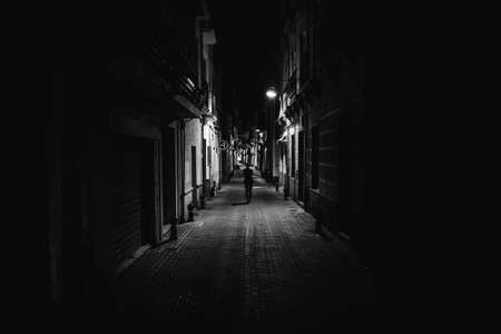 Woman walking alone in the street late at night.Narrow dark alley,unsafe female silhouette.Empty streets.Woman pedestrian alone.Police hour.Assault situation,violence against women concept. Stock Photo