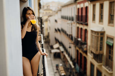 Young european woman spending free time home.Self care,staying home.Enjoying view on the balcony.Relaxing at home.Hotel room balcony view,vacation in Europe.Drinking orange juice in the morning