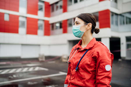 Paramedic in front of isolation hospital facility.Coronavirus Covid-19 heroes.Mental strength of medical professional.Emergency room doctor prepared for virus outbreak.Ready for hard work.Brave nurse Stock Photo