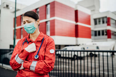 Crying paramedic in front of isolation hospital facility.Mental melt down of medical professional.Emergency room doctor in fear and stress,pressure of fight against corona virus.Covid-19 deaths impact Stock Photo