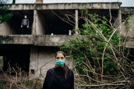 Two people in masks in a abandoned location.Abandoned city ruins. Divided by incurable infectious disease,catastrophe.Isolation.Loved one illness,distance.