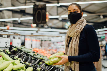Young woman wearing protective face mask shopping in a supermarket,buying organic produce.Eating healthy food during coronavirus COVID - 19 pandemic.Healthy green zucchini.Grocery shop Standard-Bild - 161231872