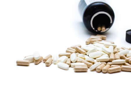 White and brown capsules spilling from a bottle of a prescription; shallow depth-of-field image. Isolated over white background.