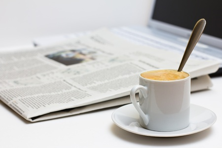 Cup of coffee and newspaper over laptop. photo