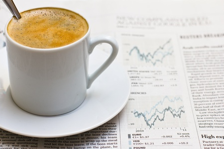Cup of coffee over financial section of a newspaper.