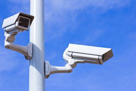 Two surveillance cameras on a pole, blue sky.
