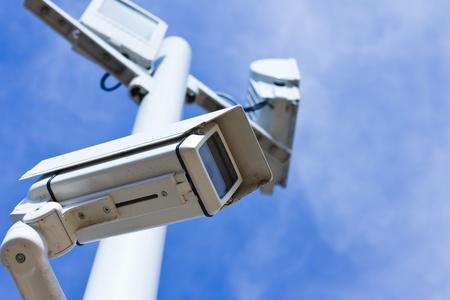 Cámara de vigilancia en un polo, vista de ángulo bajo, cielo azul.