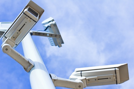 Two surveillance cameras on a pole, low angle view, blue sky. photo