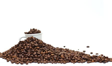 A espresso cup buried with dark roasted coffee beans, on a coffee mountain with limited depth of field (shallow DOF), isolated on white. Stock Photo - 9212975