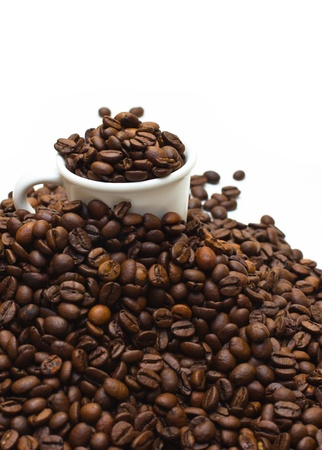 Upper view of a espresso cup buried with dark roasted coffee beans, on a coffee mountain with limited depth of field (shallow DOF), isolated on white. photo