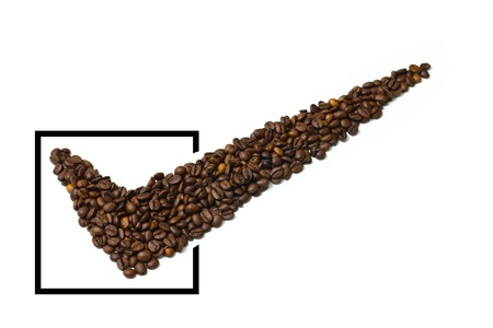 Dark roasted coffee beans in the shape of a check mark in a black rectangle with limited depth of field, isolated on white.