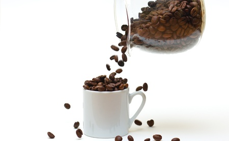 A coffee jug pouring coffee beans into an already full espresso cup with limited depth of field (shallow DOF), isolated on white.