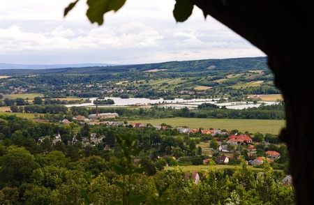 Rural view from a hill of a typical hungarian village  surrounded by fully green nature.